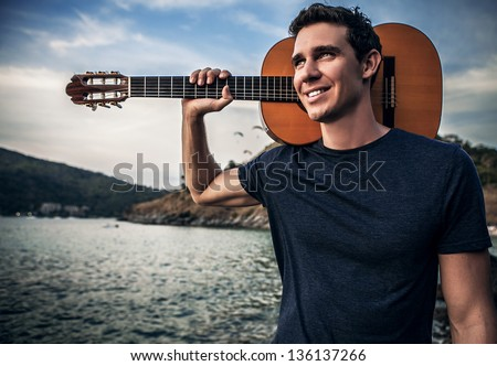 Handsome smiling man pose near evening beach with guitar. - stock photo