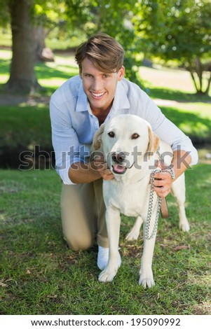 Handsome smiling man posing with his labrador in the park on a sunny day - stock photo