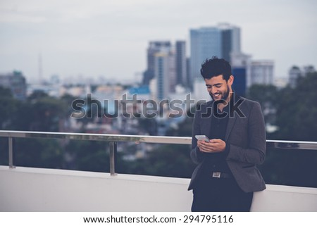 Handsome smiling man reading text message on his smartphone - stock photo