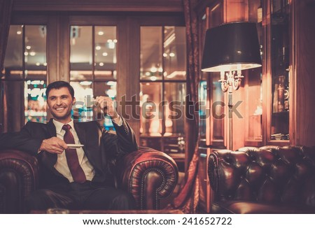 Handsome smiling man sitting with a cup of coffee in a luxury interior  - stock photo