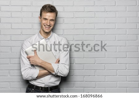Handsome smiling man standing on Grey wall background, with Laptop, Looking camera - stock photo
