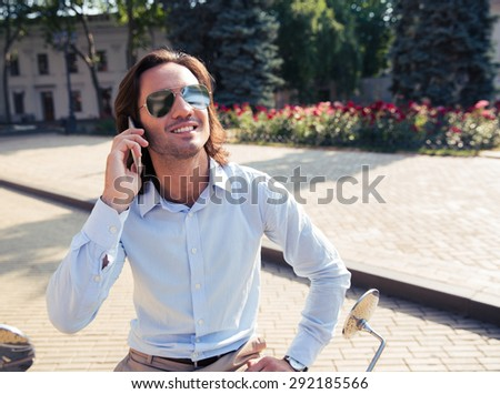 Handsome smiling man talking on the phone outdoors - stock photo