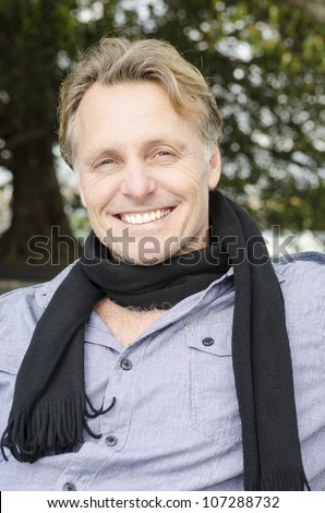 handsome smiling mature blond man wearing a black scarf and blue shirt. - stock photo