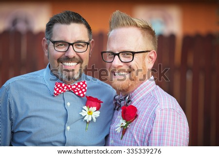Handsome smiling mature couple with eyeglasses standing outdoors - stock photo