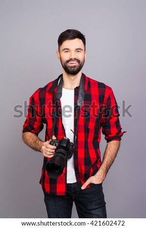 Handsome smiling photographer with camera on gray background - stock photo