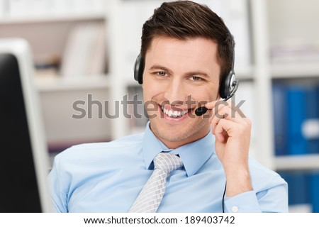 Handsome smiling young businessman using a headset conceptual of a call centre, client services, telemarketing or hands free office communication - stock photo
