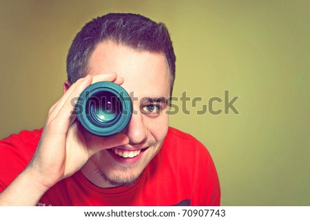 Handsome smiling young man holding camera lens like it was spyglass - stock photo