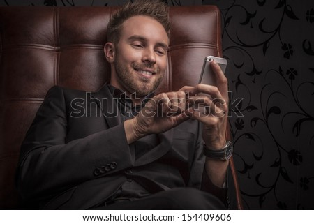 Handsome smiling young man in dark suit with phone relaxing on luxury sofa. - stock photo