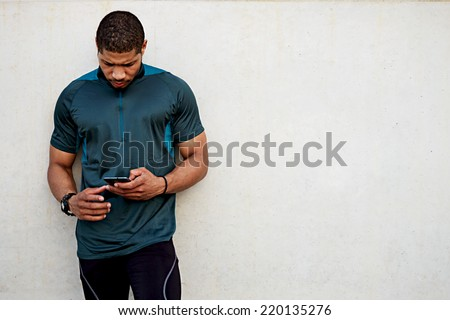 Handsome sportsman holding mobile phone and looking for the mobile screen standing outdoors, muscular build dark skin runner resting after run use his mobile phone, male runner using mobile phone - stock photo
