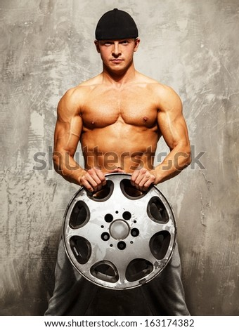 Handsome sporty man with muscular body holding alloy wheel - stock photo