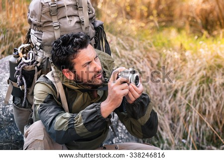 Handsome squatting hicker portrait with vintage camera, he is looking to the side. Young man in the forest. Active lifestyle, tourism in nature. - stock photo