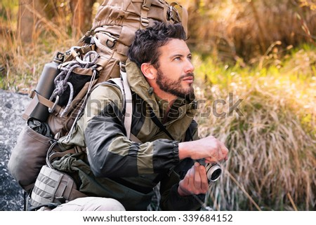 Handsome squatting hiker portrait with vintage camera, he is looking to the side. Young man in the forest. Active lifestyle, tourism in nature. - stock photo