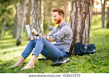 Handsome student reading and studying in park