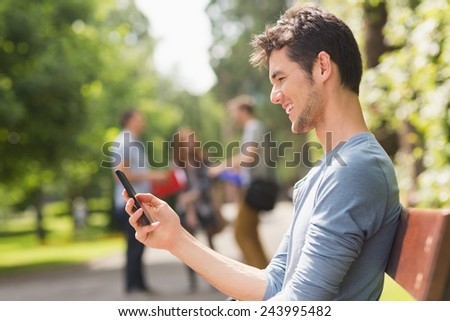 Handsome student sending a text outside at the university - stock photo