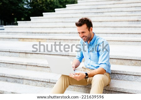 Handsome student sitting on stone stairs and using a laptop - stock photo