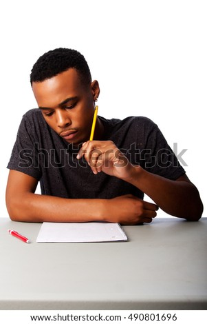 Handsome student thinking concentrating focussing for test examination sitting at desk, on white.