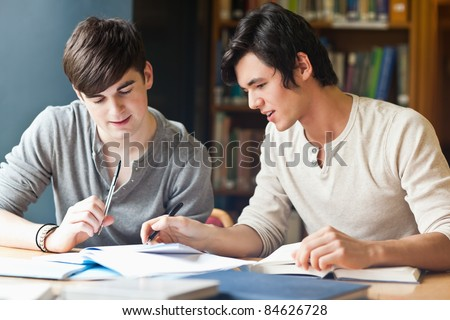 Handsome student working on an essay in the library - stock photo
