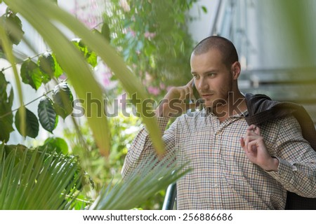 Handsome stylish businessman speaking on the phone in office - stock photo
