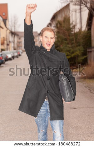 Handsome stylish successful urban man cheering as he walks down a street in town with a brief case under his arm and his arm raised in jubilation / Handsome successful urban man cheering - stock photo