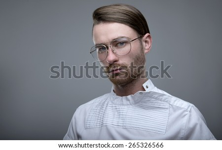 Handsome stylish young man. A man with a beard wearing glasses looking at the camera
