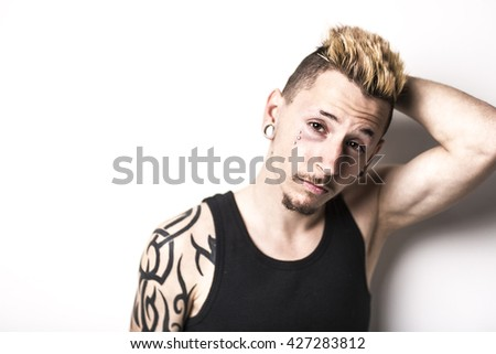 Handsome stylish young man with tattoo and piercing