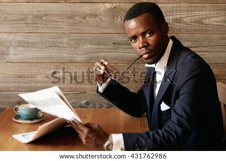 Handsome successful African corporate worker wearing elegant formal suit, looking at the camera with serious confident expression, holding glasses at his mouth, having coffee and reading newspaper - stock photo