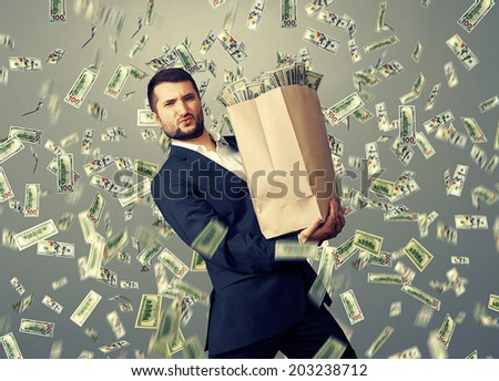 handsome successful businessman holding heavy paper bag with money under dollar's rain - stock photo