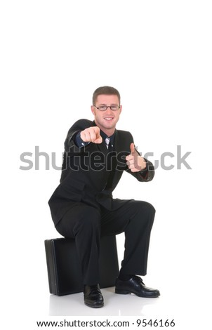 Handsome successful young businessman, sitting on briefcase, joyful expression, studio shot.