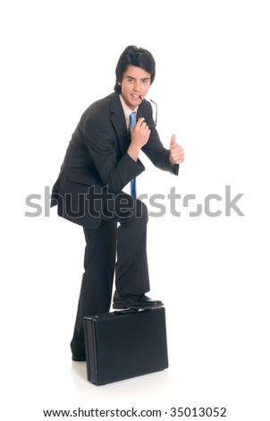 Handsome successful young businessman with briefcase, joyful expression, studio shot.