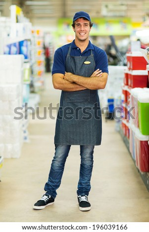 handsome supermarket worker with arms crossed - stock photo