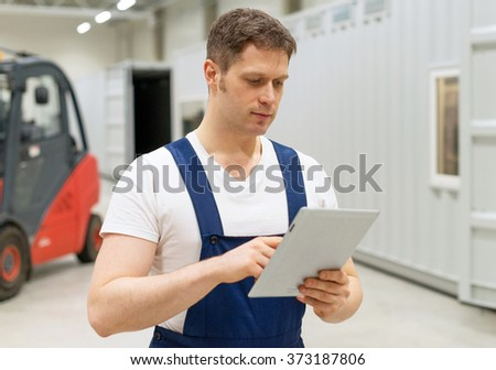 Handsome supervisor with tablet pc at the warehouse. Place for text. - stock photo