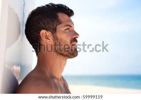 Handsome surfer looking at the sea with his board behind him. Side view - stock photo