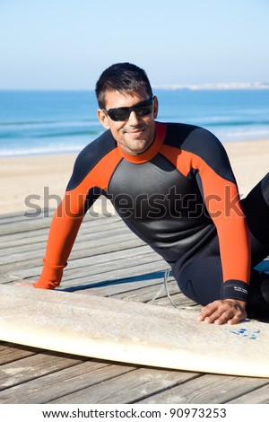 Handsome surfer wearing a wetsuit sitting next to his surf board smiling at camera.