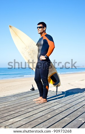 Handsome surfer wearing sunglasses and a wetsuit standing with his surf board. - stock photo