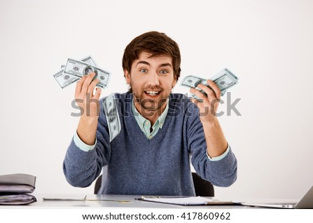 Handsome surprised confident young businessman sitting at the office desk holding stack of cash in his hands. Looking at camera. Isolated on white background. - stock photo