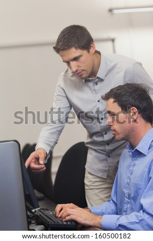 Handsome teacher talking to a student in computer class