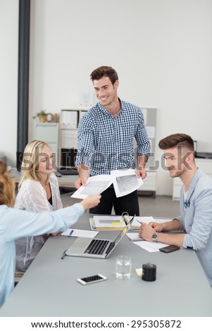 Handsome Team Leader Distributing Some Documents to Members While Having a Business Meeting Inside the Boardroom - stock photo