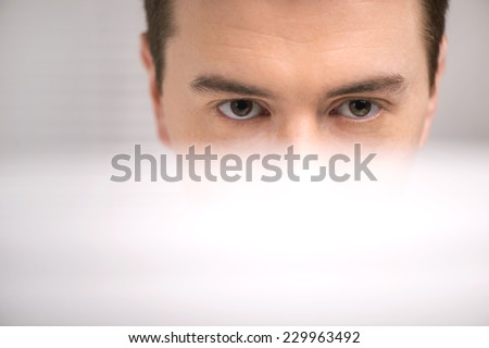 handsome technical support operator working on computer. male eyes behind computer at bright center helpdesk support office  - stock photo