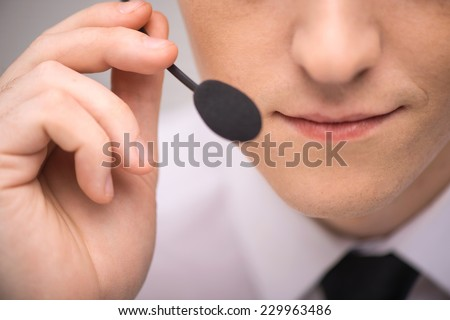 handsome technical support operator working on computer. male mouth with headset portrait holding mic - stock photo