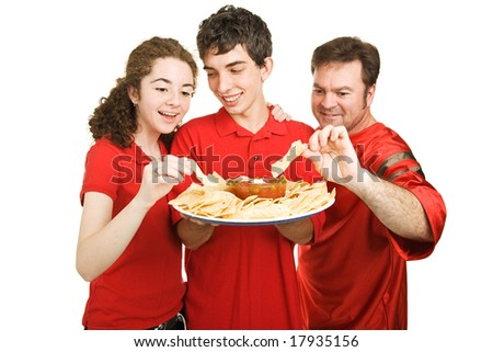 Handsome teen boy serves chips at a football party.  Isolated on white. - stock photo