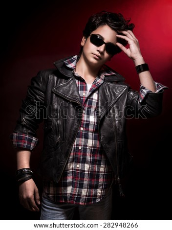 Handsome teen boy wearing stylish sunglasses and leather jacket over dark red background, teenage fashion and style