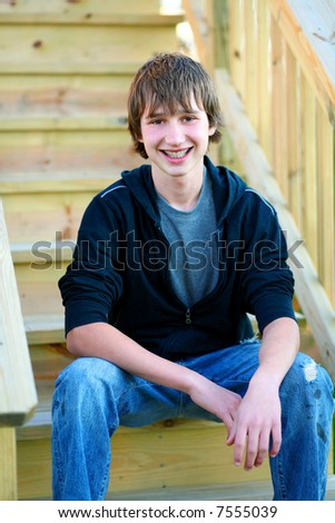 handsome teen guy model seated on stairs smiling