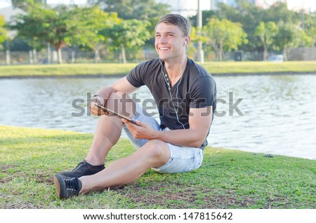 Handsome teen using white earphones and listening to music in a park outdoors - stock photo