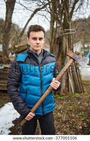 Handsome teenage country boy holding axes outdoor - stock photo