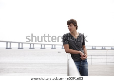 handsome teenager with a sad face next to the river - stock photo