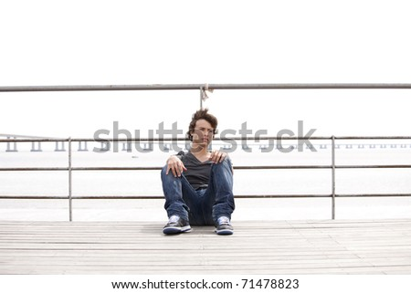 handsome teenager with a sad face sited next to the river - stock photo