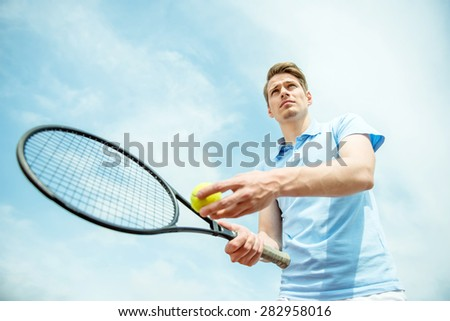 Handsome tennis player on hard court serving the ball. - stock photo