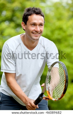 Handsome tennis player with his racket outdoors - stock photo