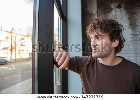 Handsome thoughtful guy in brown sweetshirt staring at the window - stock photo