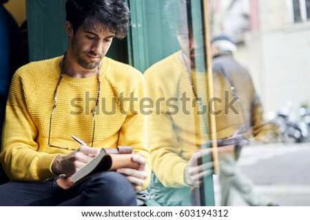 Handsome thoughtful male writer noting best ideas for magazine article about restaurant review planning strategy in personal diary organizing ideas to create successful material for front page